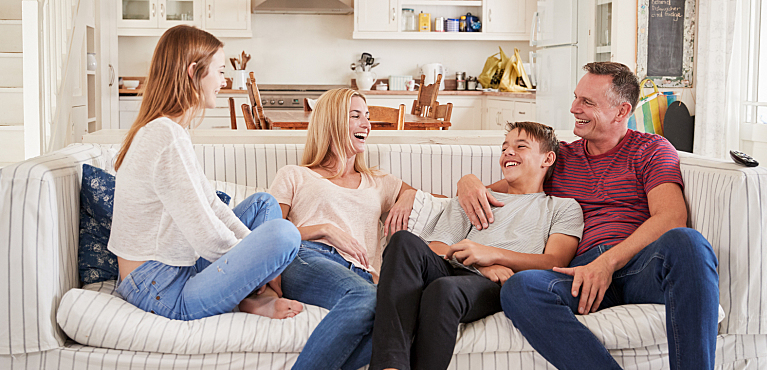 Happy mother, father, son and daughter discussing family finances on the couch at home