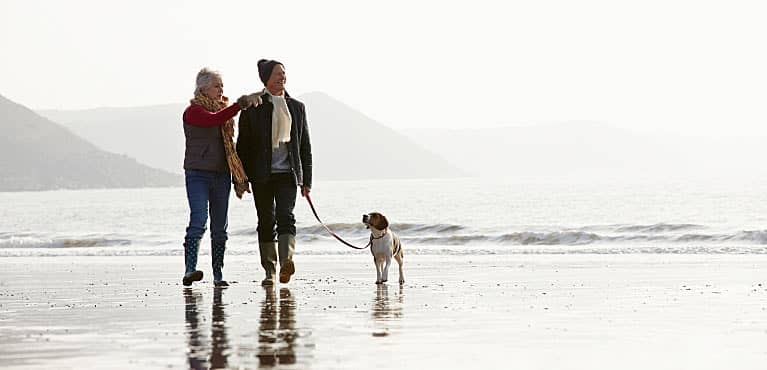 How much do I need to retire at 60, like the couple pictured here walking on the beach?