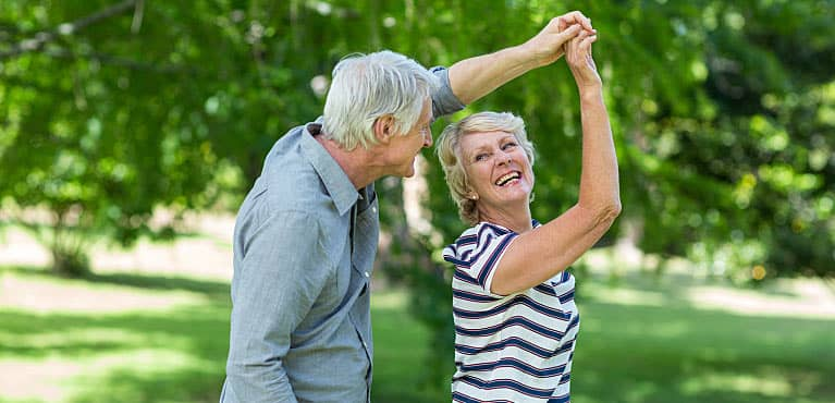 One of many happy married couples with Social Security benefits dancing together in the park