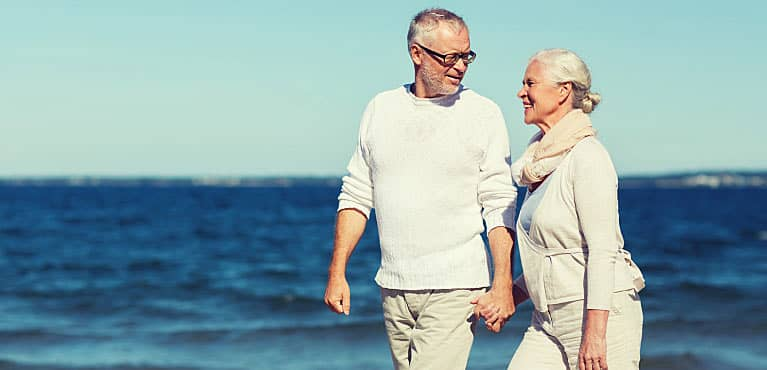 Senior couple knowledgeable about the difference between Medicare vs. Medicaid walking on the beach.