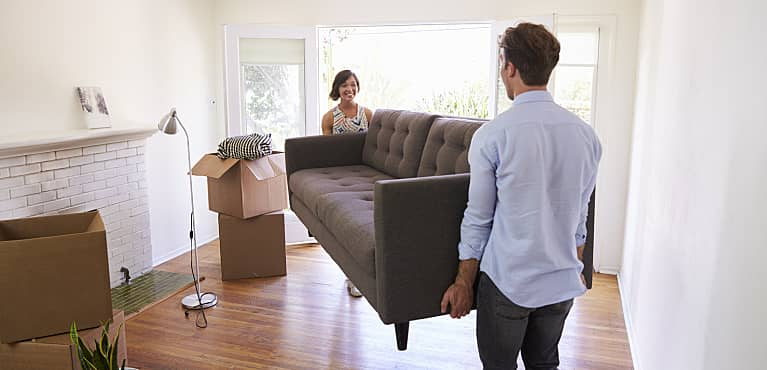 Young couple carrying a sofa into the living room of their new house