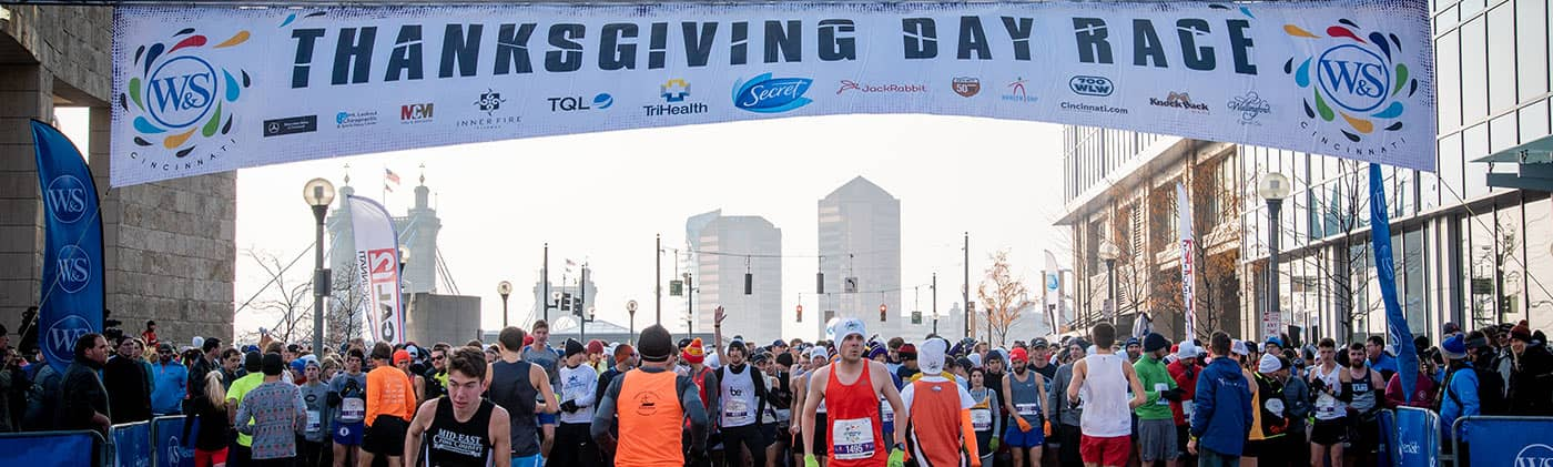 runners preparing for thanksgiving day race under starting line banner with participating company sponsors
