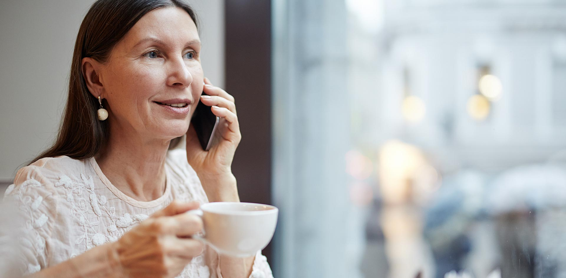 Woman talking to her husband on the phone at a cafe